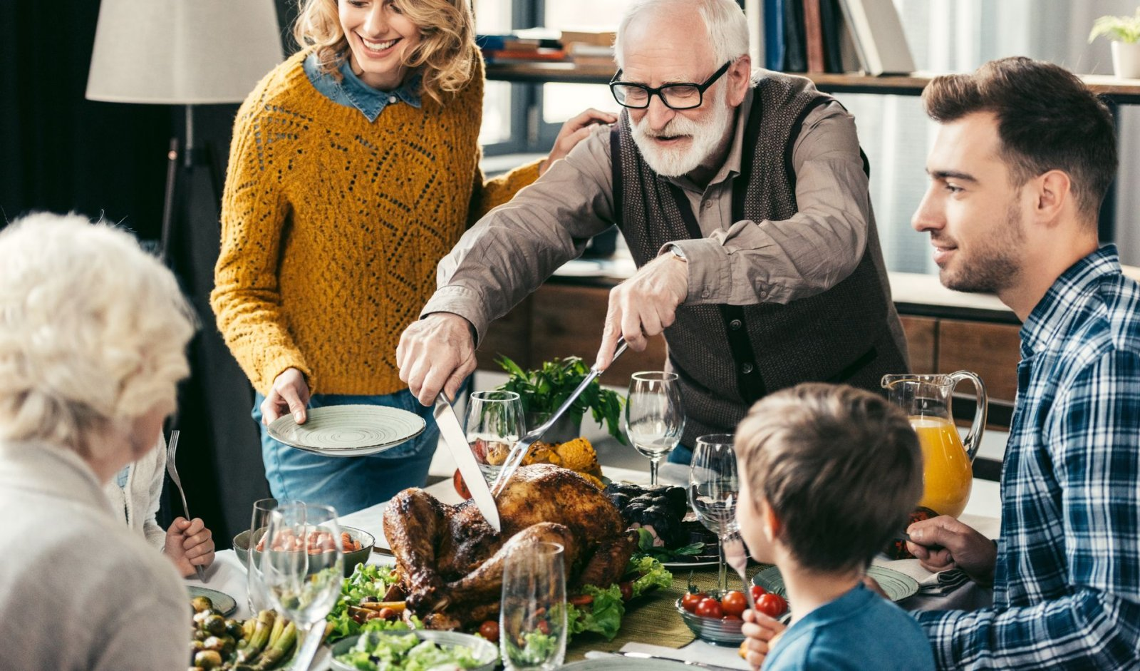 grandfather-cutting-turkey-for-family-on-thanksgiv